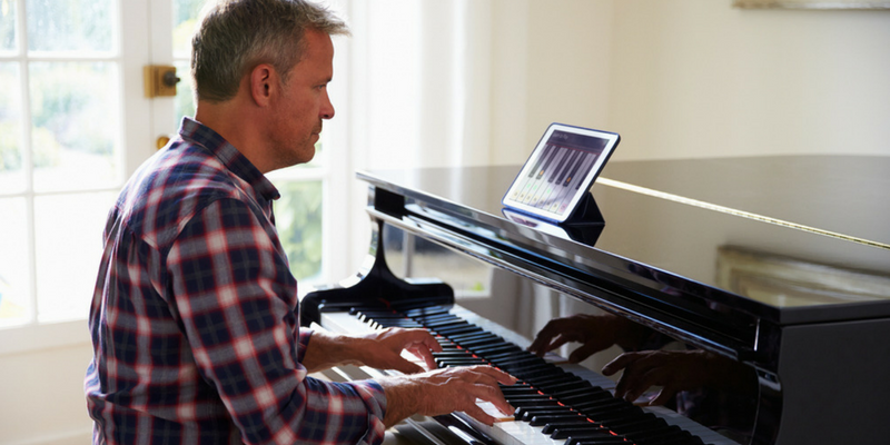 man playing piano and taking piano lessons